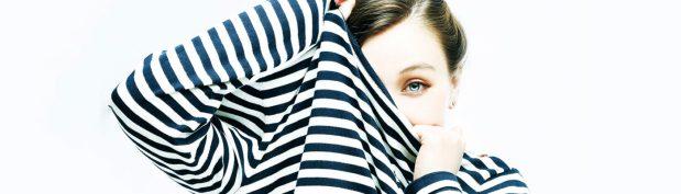 Girl  tucking herself in  striped  sweater