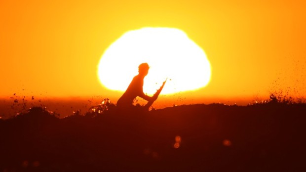 A surfer pulls off a wave as the sun sets in Cardiff during what local media reported to be a record breaking heat wave in Southern California