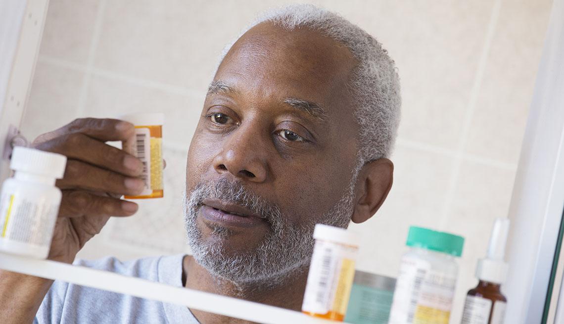 Black man examining prescription bottle in medicine cabinet
