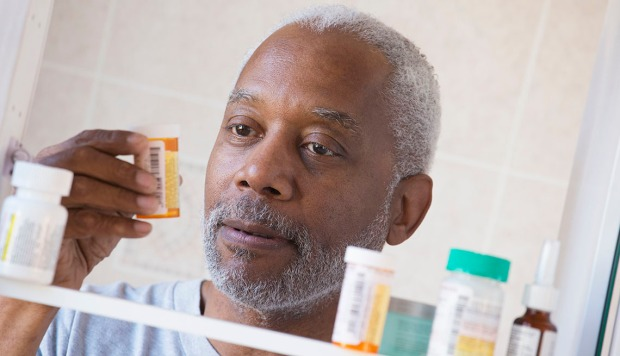 Black man examining prescription bottle in medicine cabinet